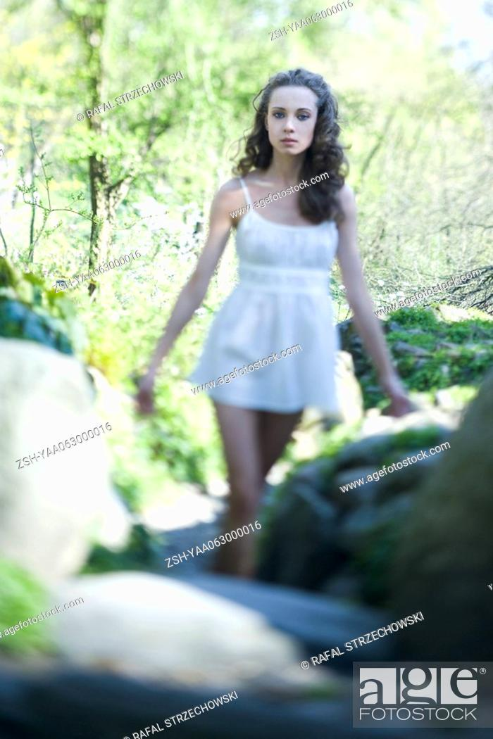Stock Photo: Young woman in slip walking outdoors, arms out, looking at camera.