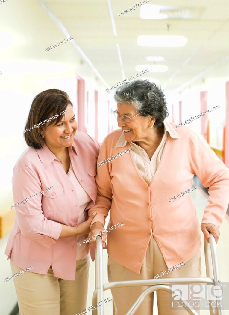 Stock Photo: Hispanic woman helping mother walk.