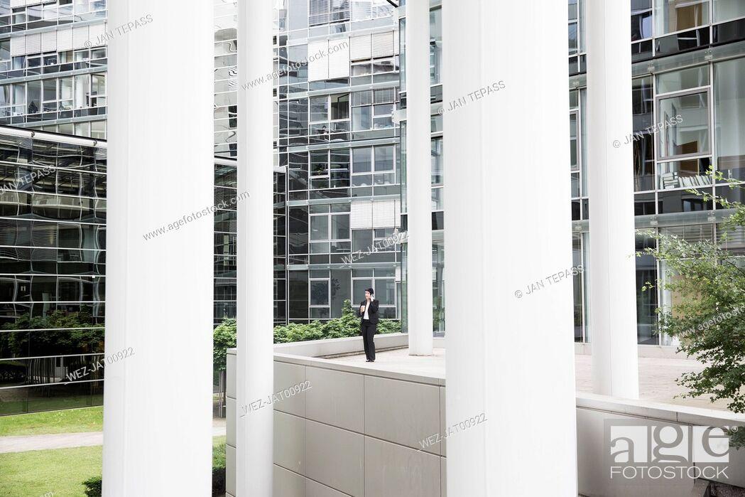 Imagen: Businesswoman standing in front of office building, usind smart phone.