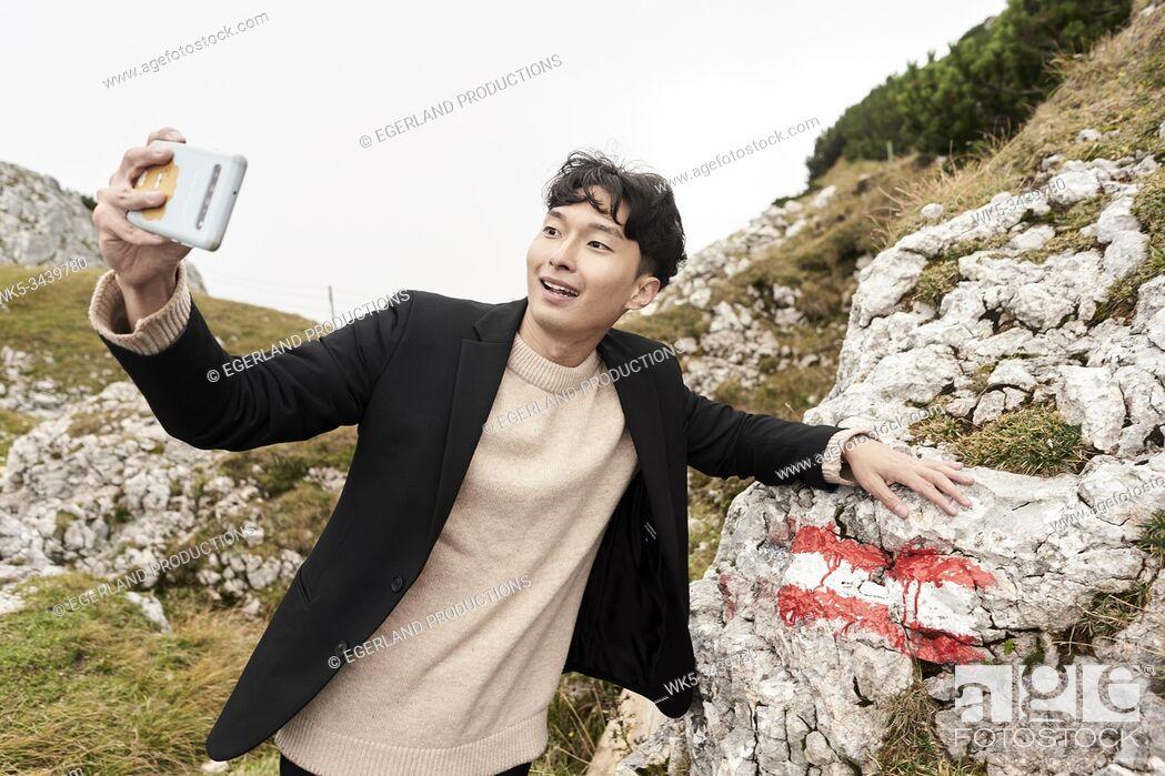 Imagen: Korean man taking selfie with Austrian flag on rock at mount Untersberg near Salzburg, Austria, Europe.