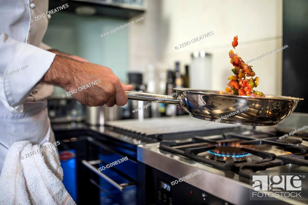 Stock Photo: Chef holding frying pan, cooking food over stove, close-up.