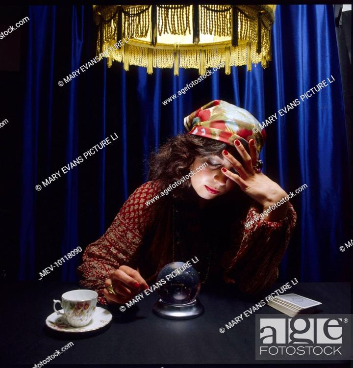 A Gypsy fortune teller gazes deeply into a crystal ball