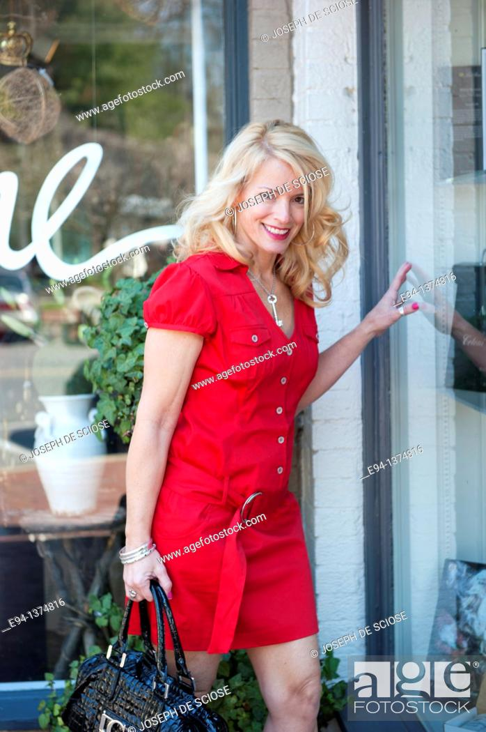Stock Photo: 44 year old blond woman wearing a red dress in an urban setting.
