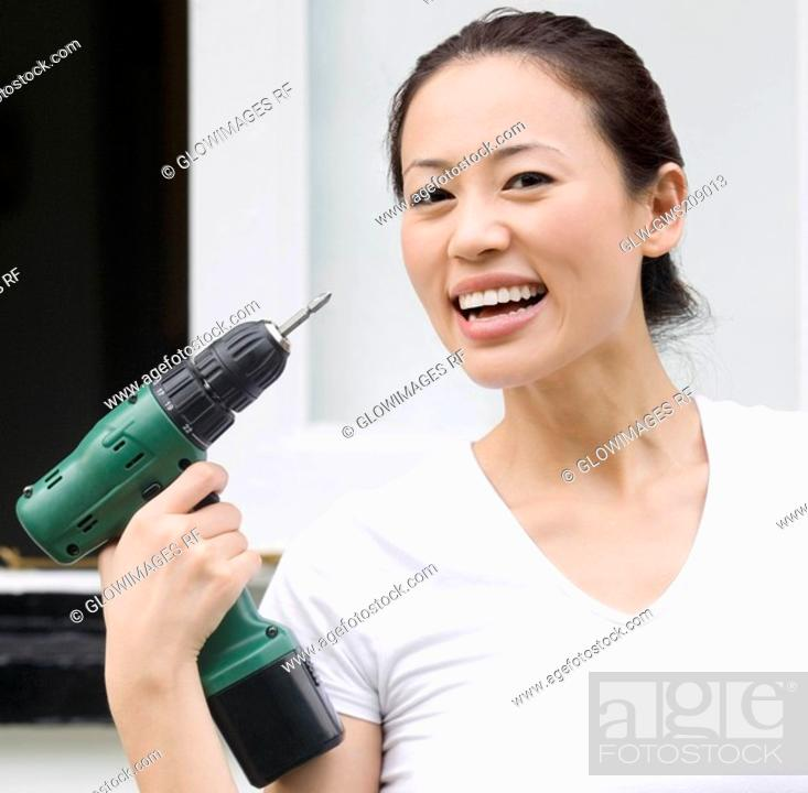 Stock Photo: Portrait of a young woman holding a hand drill and smiling.