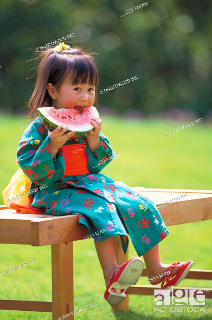 Stock Photo: Asian girl eating water melon.