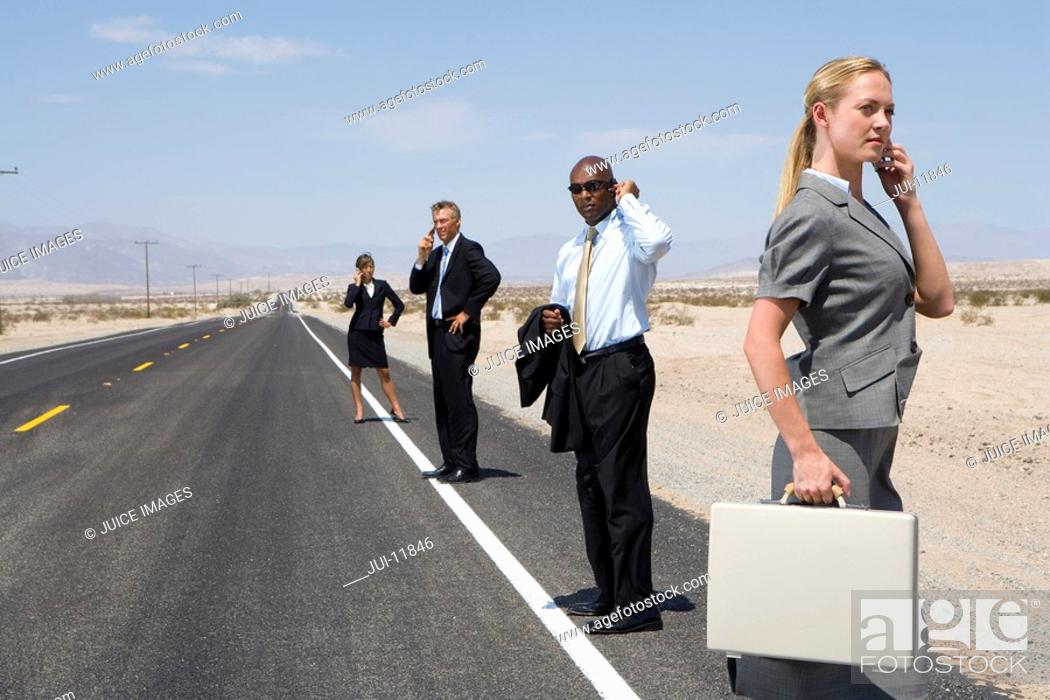 Stock Photo: Small group of businessmen and women using mobile phones on side of road in desert, side view.