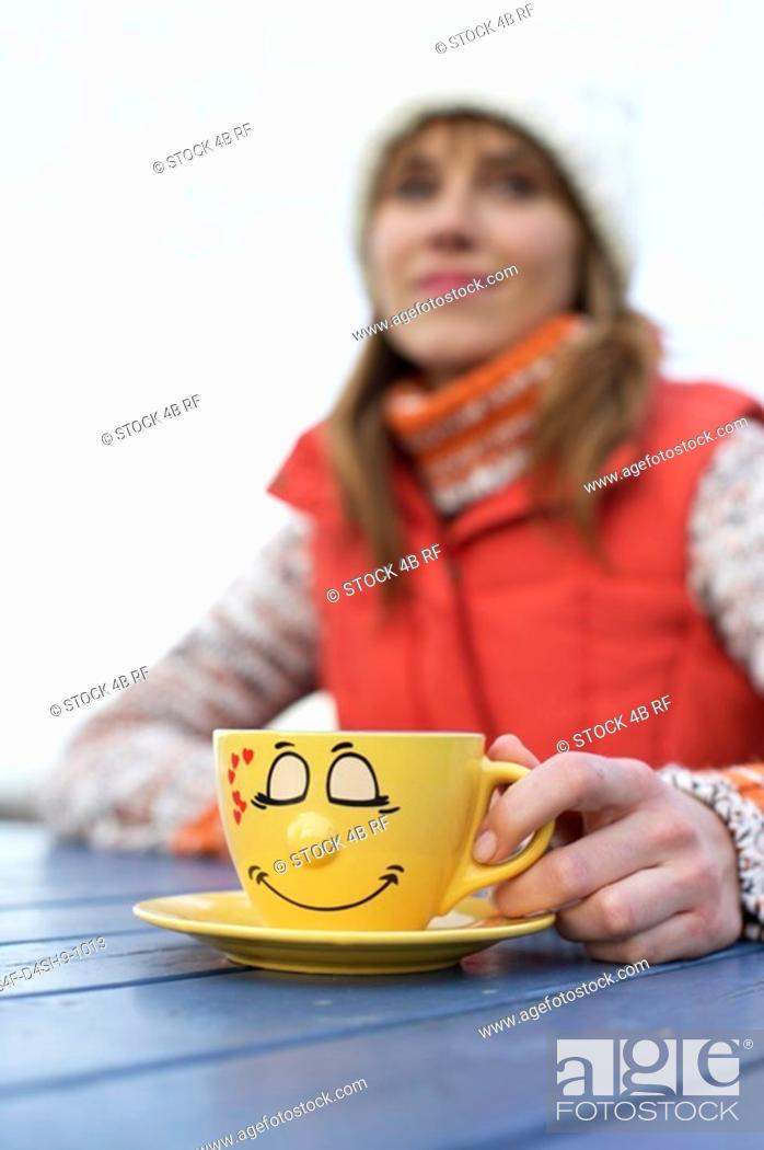 Stock Photo: Young woman in warm clothing sitting outside at a table with a painted cup in her hand, selective focus.