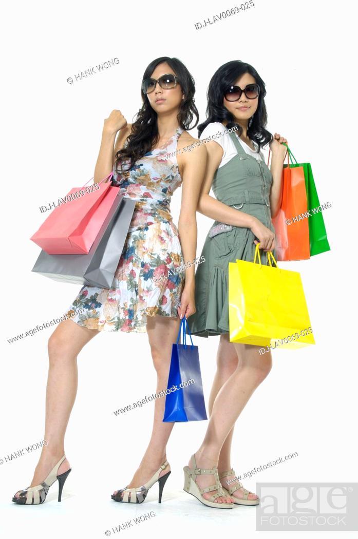 Stock Photo: Women carrying shopping bags and smirking.