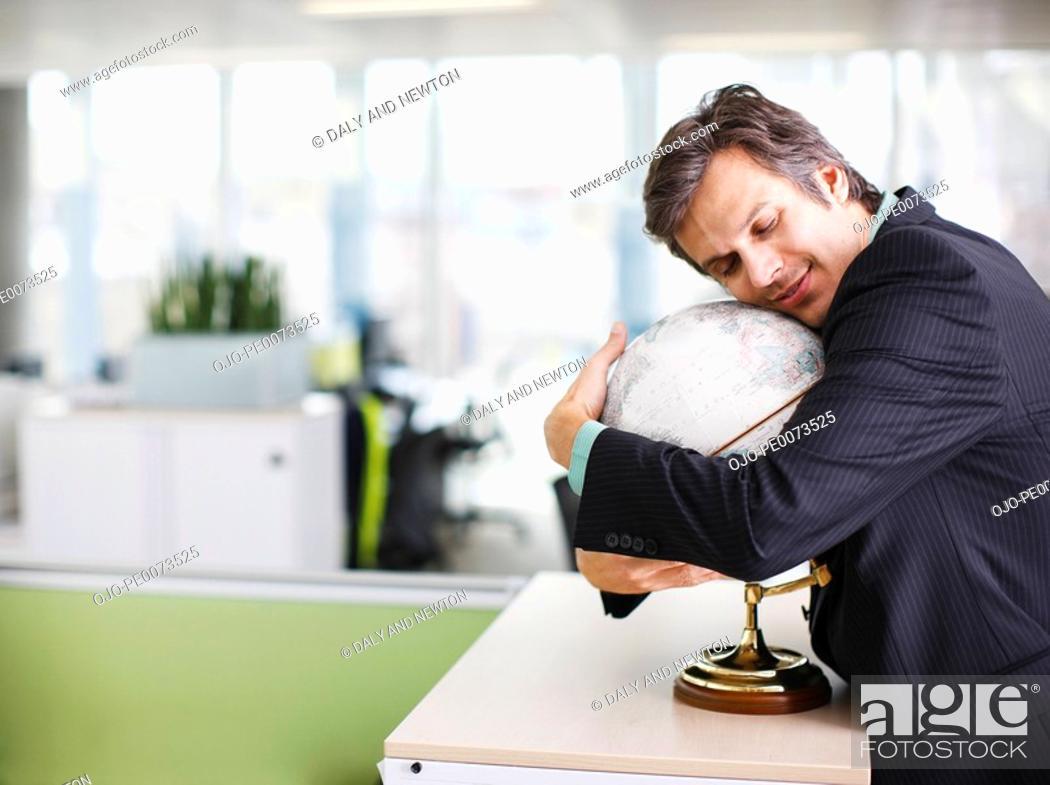 Stock Photo: Smiling businessman hugging globe in office.