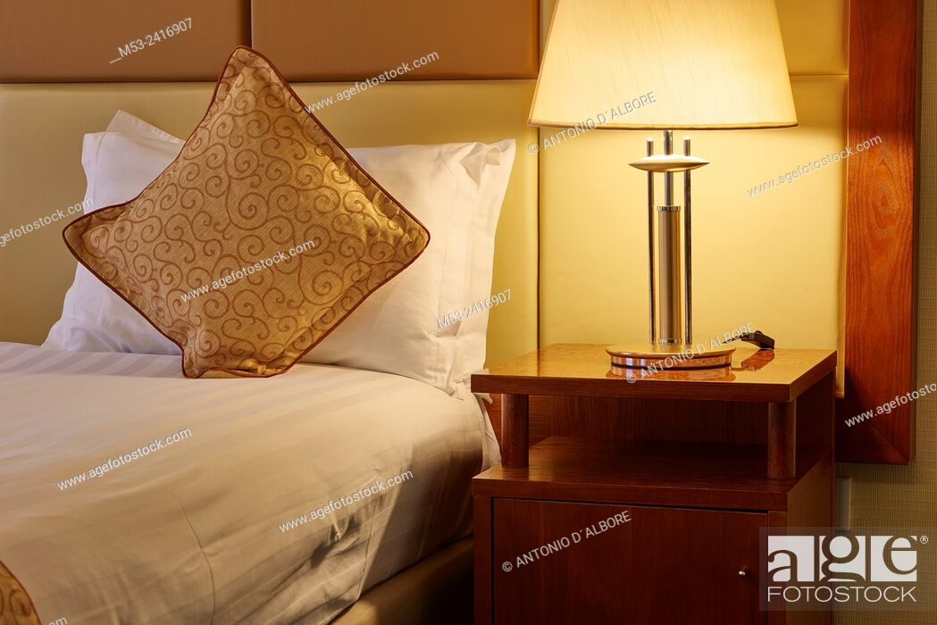 Imagen: A luxury bed with decorated pillow beside a besdide lamp.