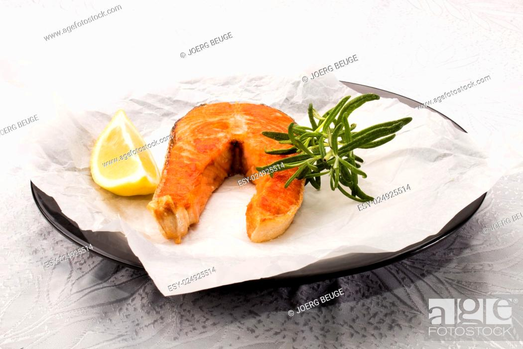 Stock Photo: fried scottish salmon steak with rosemary and white kitchen paper on a plate.