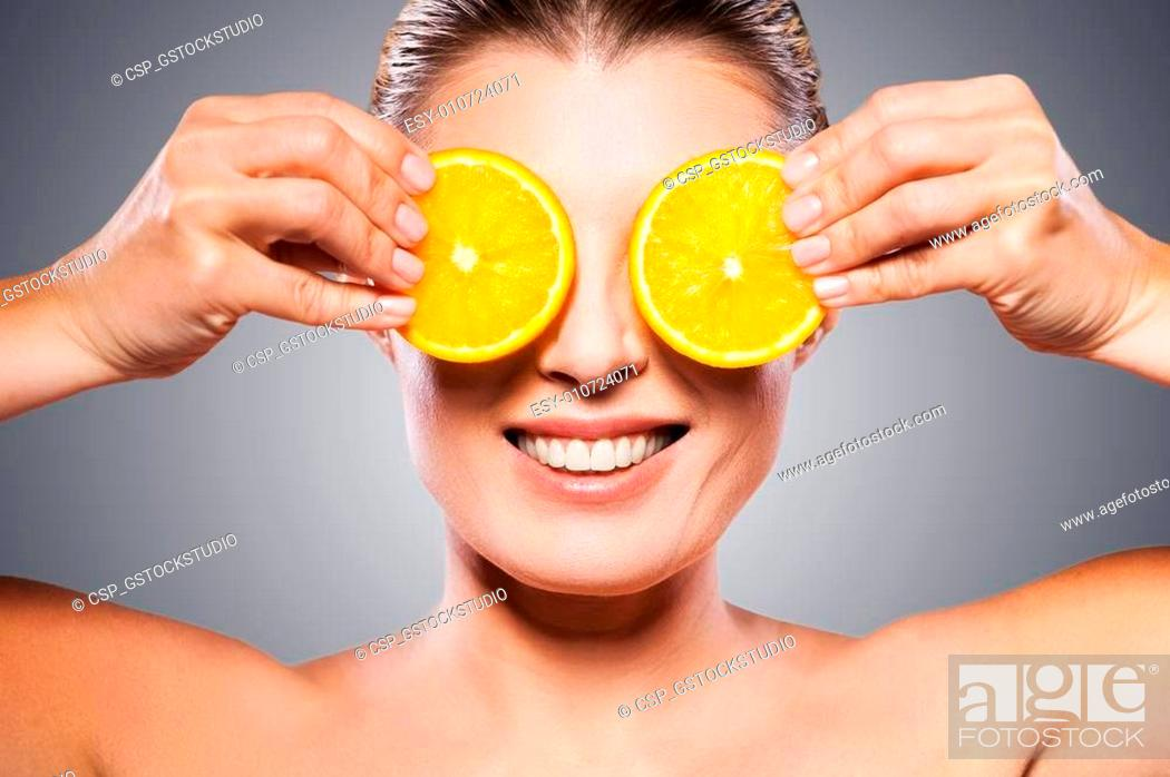 Stock Photo: Only natural ingredients. Cheerful mature woman holding pieces of orange in front of her eyes while standing isolated on white background.