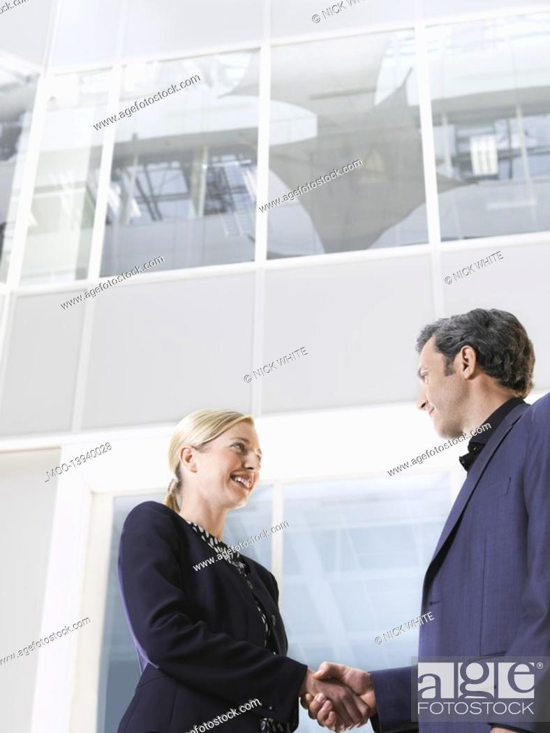 Stock Photo: Two business people shaking hands low angle view side view.