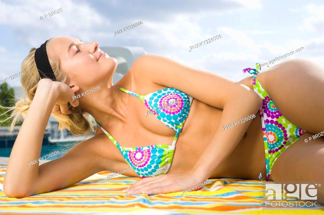 Stock Photo: Woman day dreaming at the poolside.