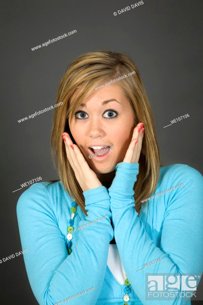 Stock Photo: Teenage girl posing on gray background with some attitude.