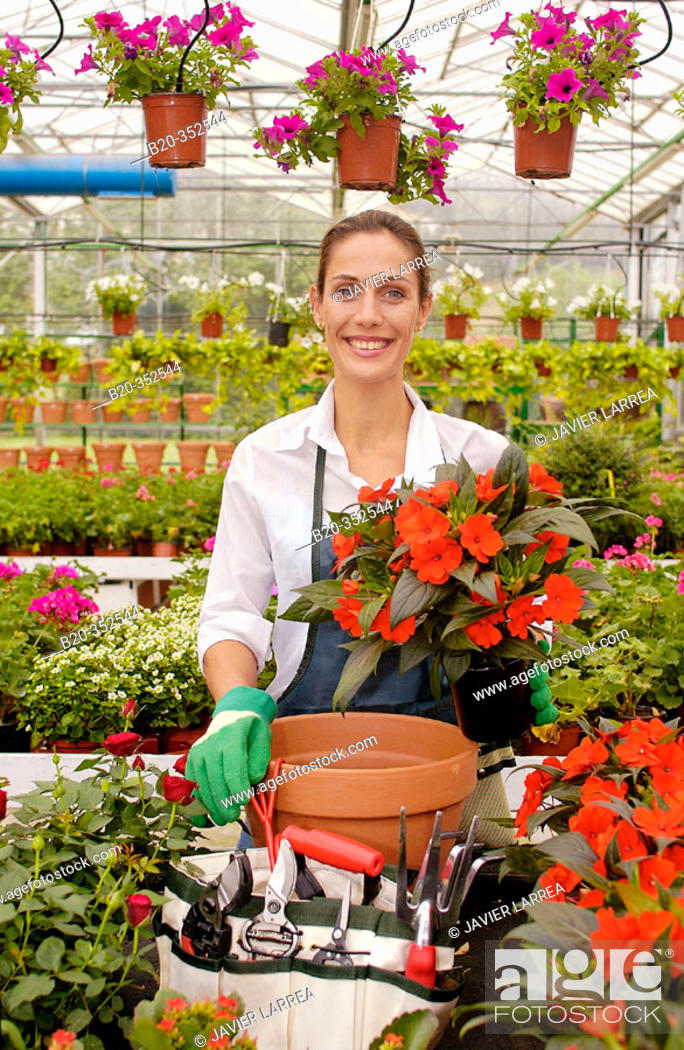 Imagen: Woman transplanting flowers in pot at garden centre.