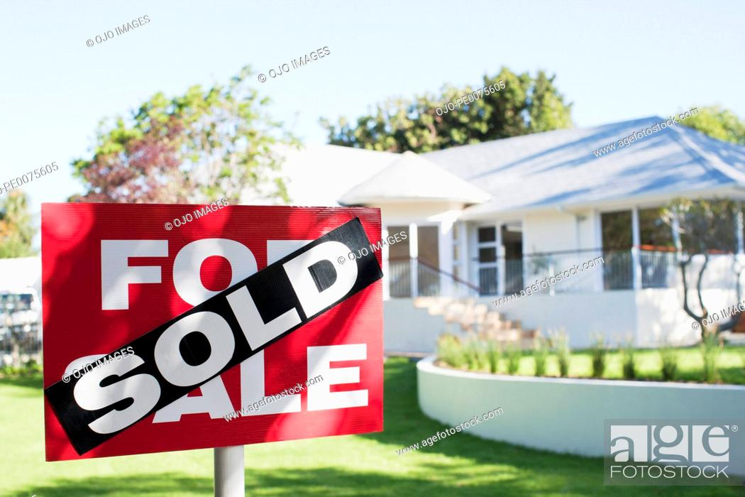 Stock Photo: Sold sign in front yard of house.