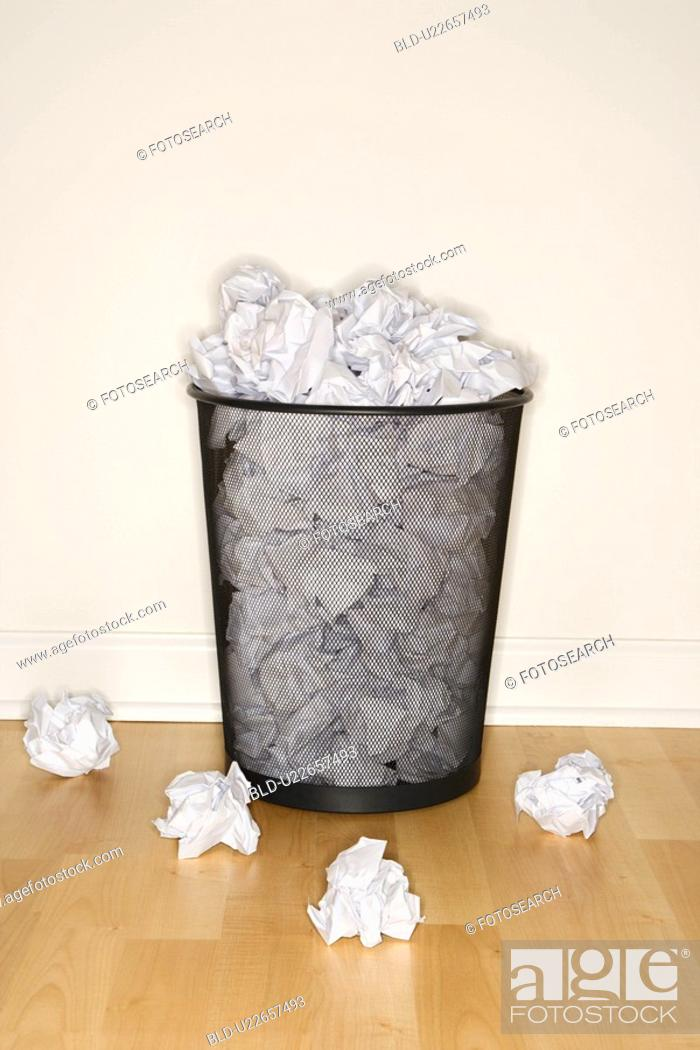 Stock Photo: Wire mesh trash can filled and surrounded by crumpled paper.
