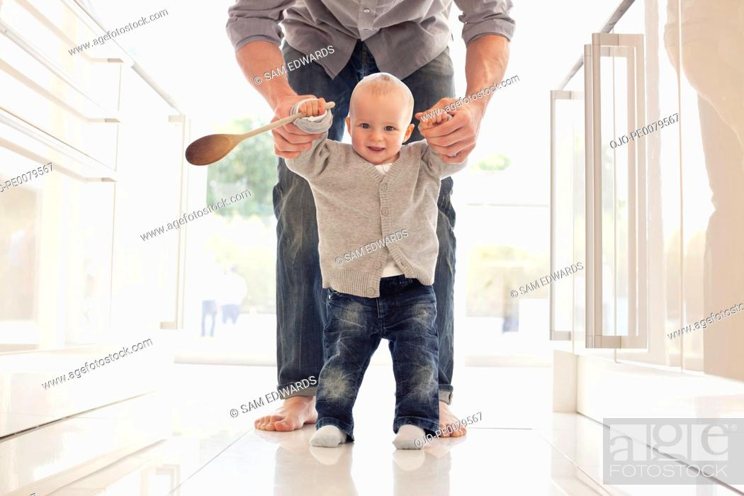 Stock Photo: Father helping son learn to walk.