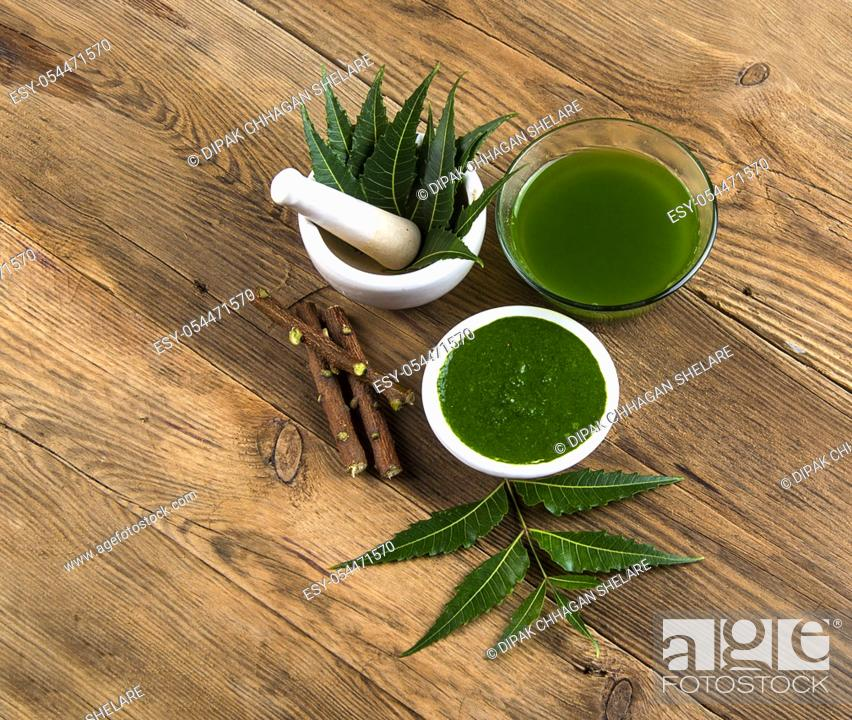 Stock Photo: Medicinal Neem leaves in mortar and pestle with neem paste, juice and twigs on wooden background.