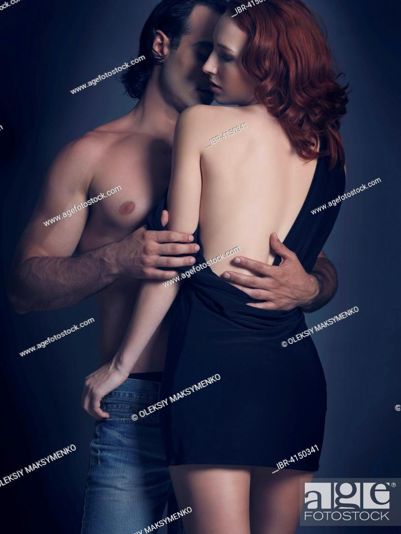 Stock Photo: Young sexy couple, man with bare torso embracing woman in backless dress.