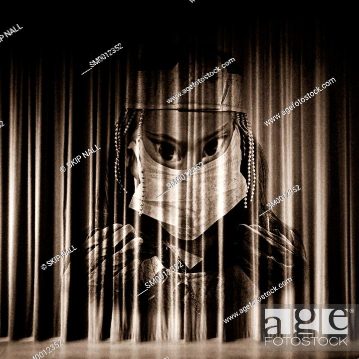 Stock Photo: A stage curtain with the face of a scary doctor appearing on it.
