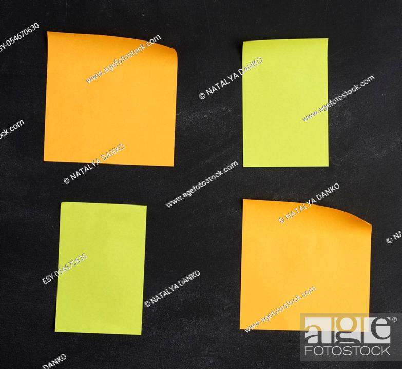 Stock Photo: blank paper multi-colored square stickers are stuck on a black chalk board, close up.