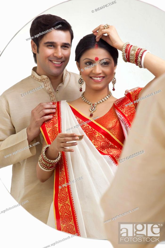 Stock Photo: Bengali woman putting sindoor on her forehead while husband watches on.