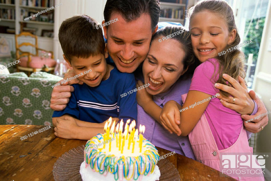 Stock Photo: Parents with their son and daughter in front of a birthday cake.