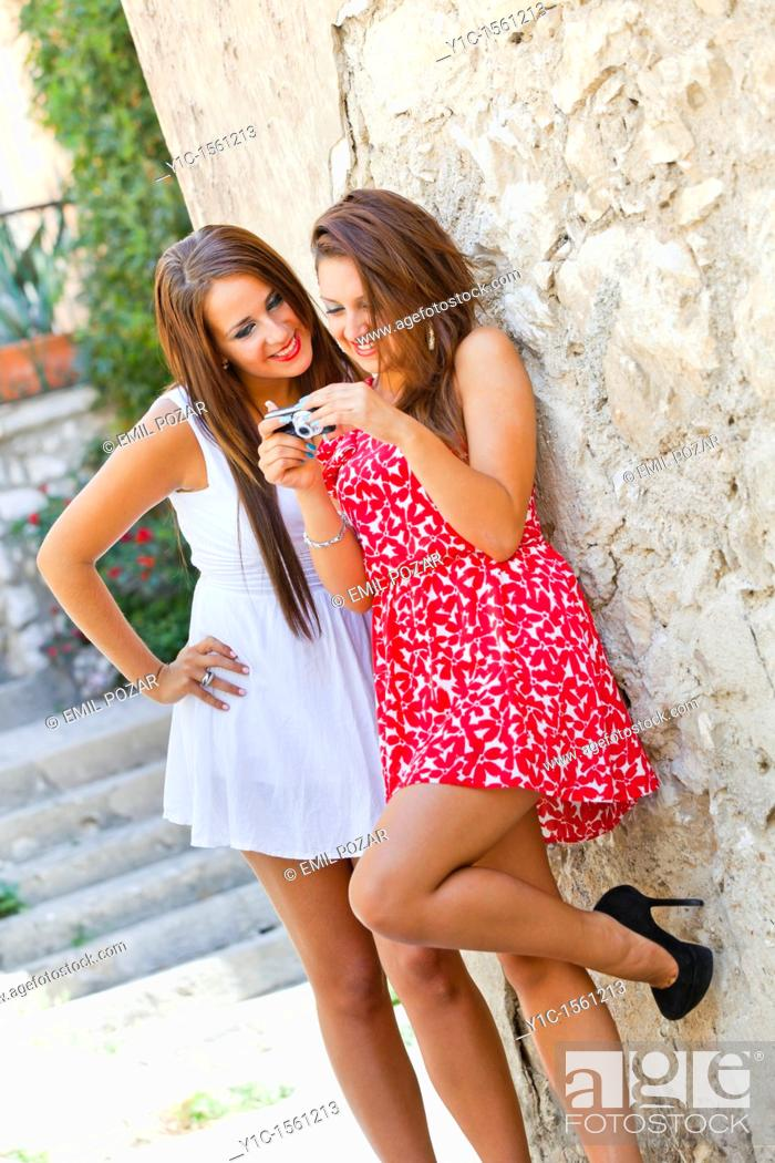 Stock Photo: Two young women are looking at photos on back of the digital camera.