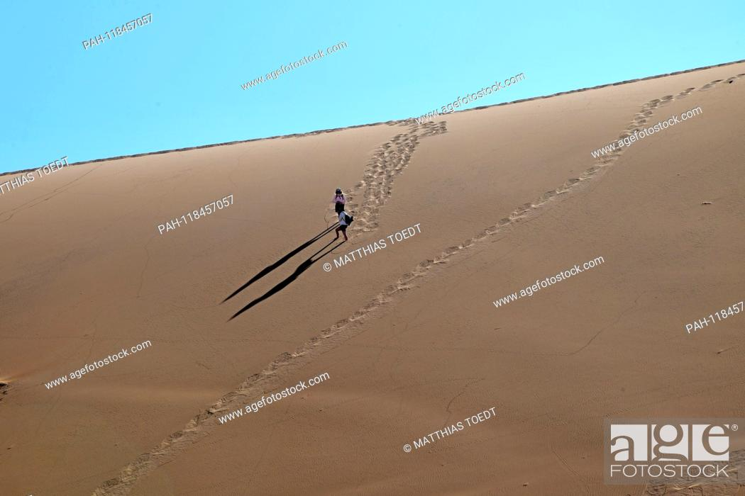 Stock Photo: Two tourists walk down the high dunes to the Dead Vlei, taken on 01.03.2019. The Dead Vlei is a dry, surrounded by tall dune clay pan with numerous dead acacia.