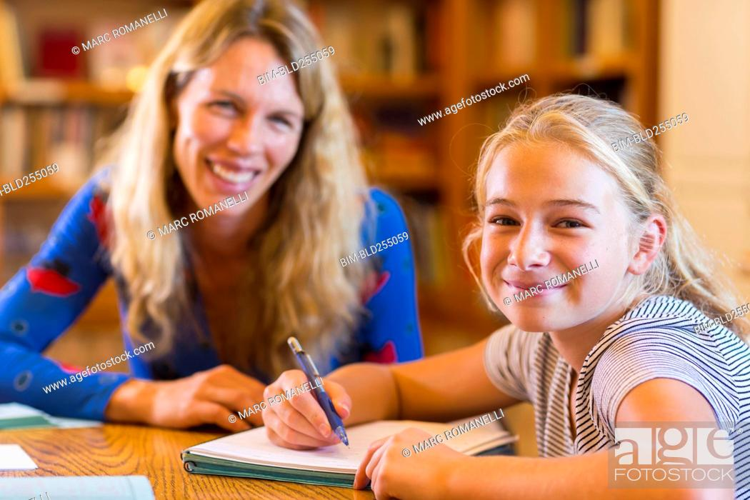Stock Photo: Portrait of Caucasian teacher helping student in library.