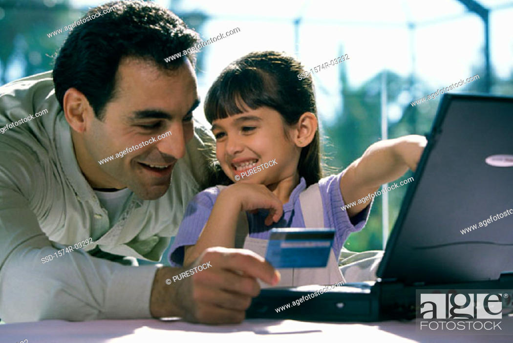 Stock Photo: Father and his daughter in front of a laptop holding a credit card.