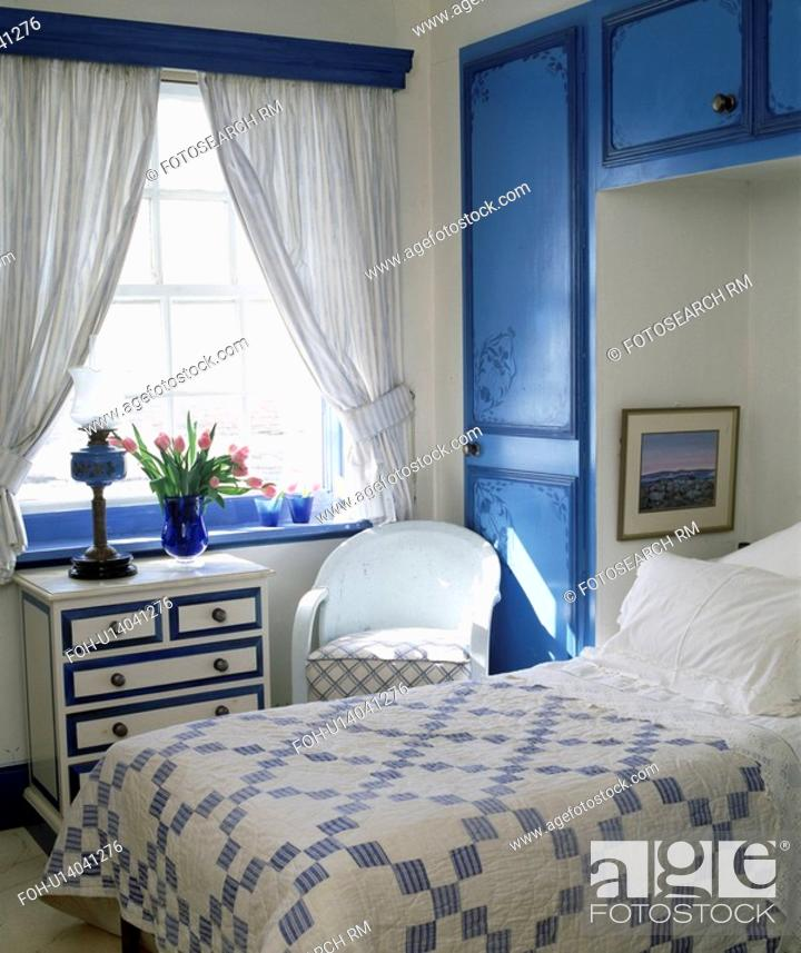 Stock Photo Blue White Patchwork Quilt On Bed In Alcove With Ed Cupboards Bedroom Curtains