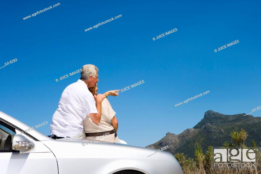 Stock Photo: South Africa, Cape Town, senior couple sitting on convertible silver car, man pointing, rear view.