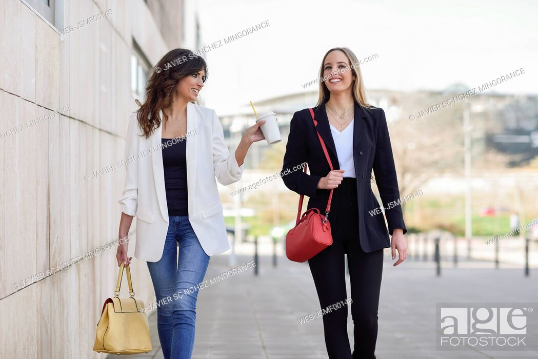 Photo de stock: Two smiling businesswomen with handbags and coffee to go walking on pavement.