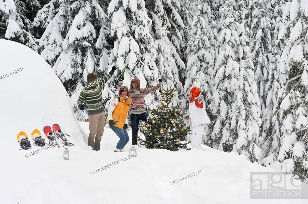Stock Photo: Austria, Salzburg, Men and women dancing by christmas tree in winter.
