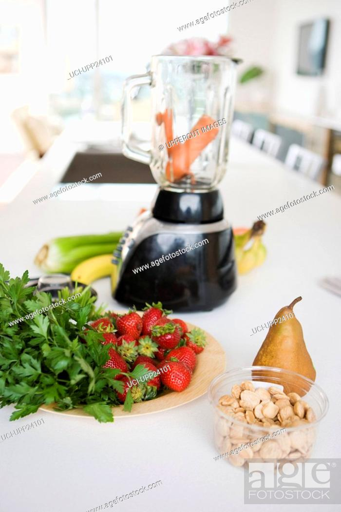 Stock Photo: Close up of fresh vegetables, fruit, and nuts near blender.