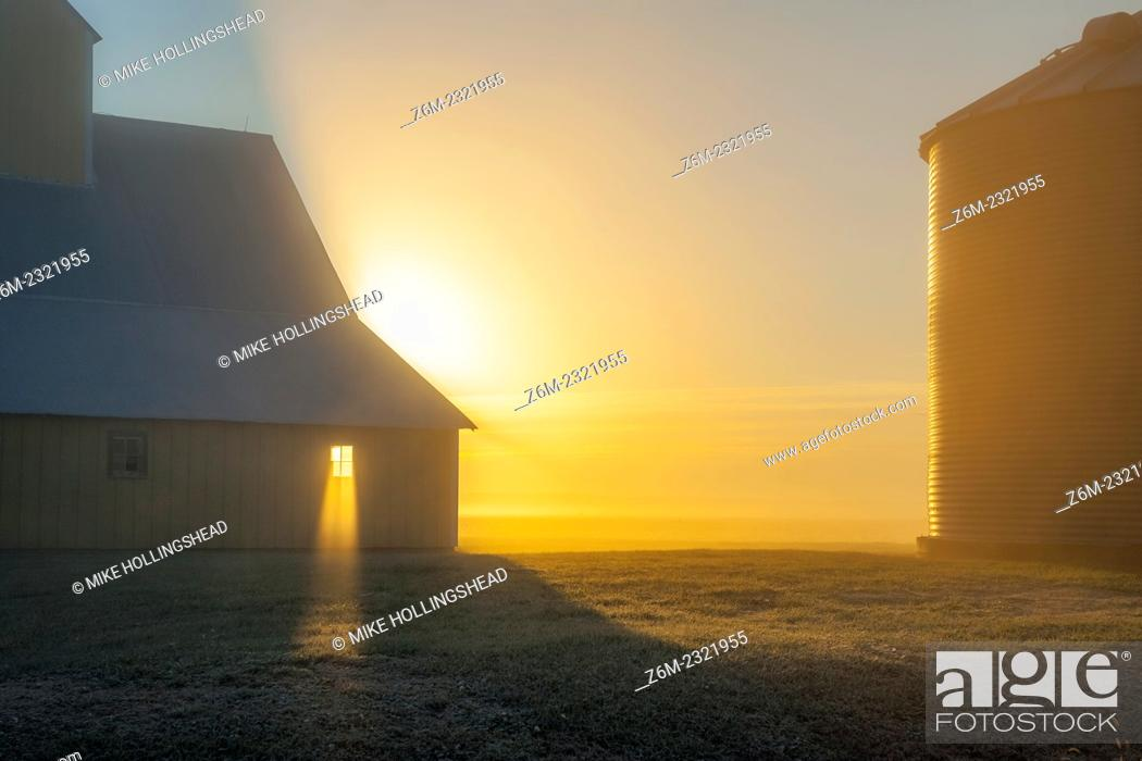 Stock Photo: Sun rays shine through barn window on foggy morning in western Iowa.