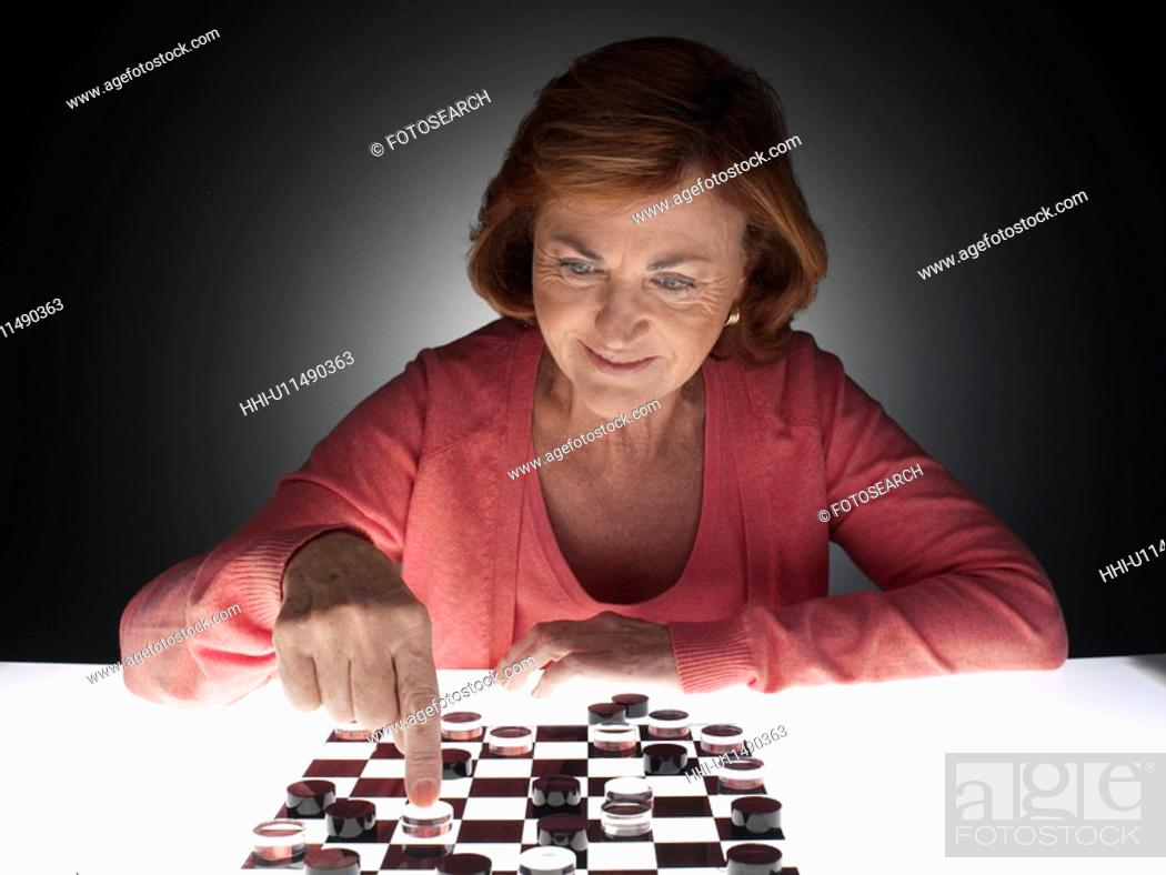 Stock Photo: Woman playing checkers.