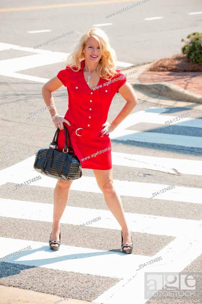 Stock Photo: A 44 year old blond woman wearing a red dress standing in the crosswalk of a city street.