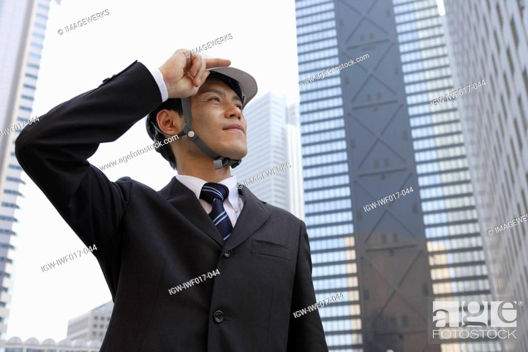 Stock Photo: Businessman holding his hard hat, portrait.