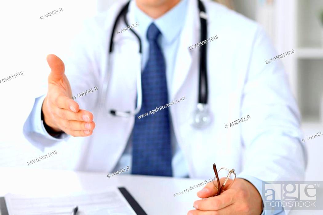 Stock Photo: Male medicine doctor offering helping hand for handshake. Partnership and trust concept.