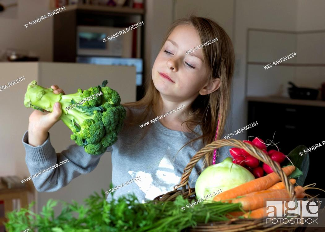 Stock Photo: Portrait of girl with wickerbasket of fresh vegetables looking at broccoli.