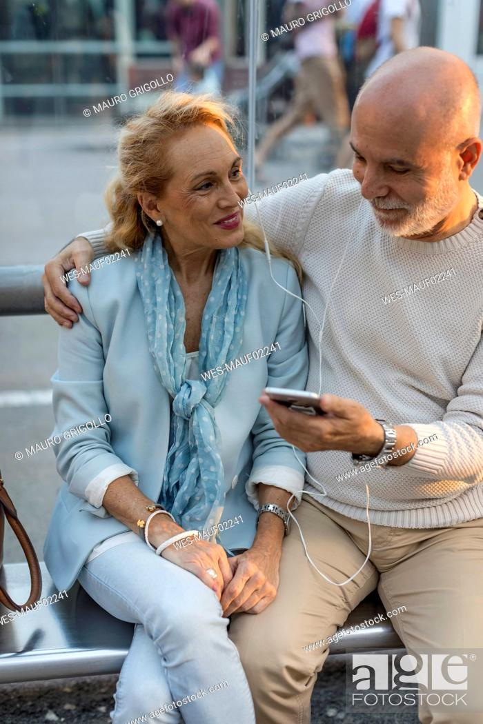 Stock Photo: Spain, Barcelona, senior couple sitting at tram stop in the city sharing smartphone with earbuds.