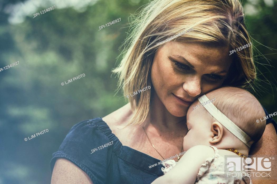 Stock Photo: A young mother cuddling her sleeping baby outdoors in a park and deep in thought about her child; Edmonton, Alberta, Canada.