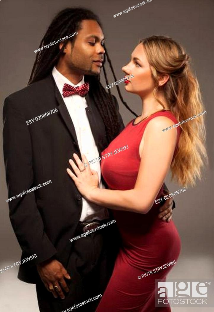 Stock Photo: Black man and Caucasian woman standing close to each other with confident look.