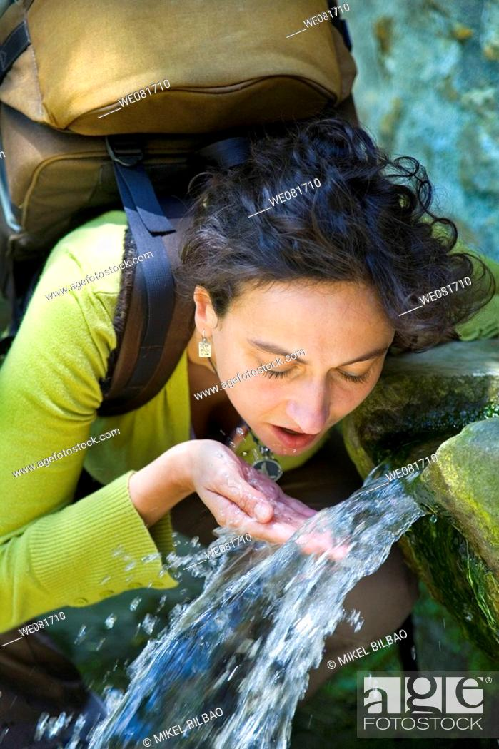 Stock Photo: Portrait of a young woman with a backpack drinking in a fountain.