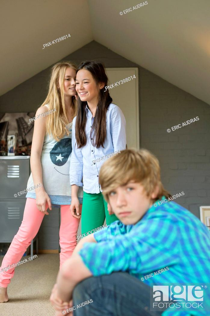 Stock Photo: Portrait of a teenage boy with his two sisters whispering in background.