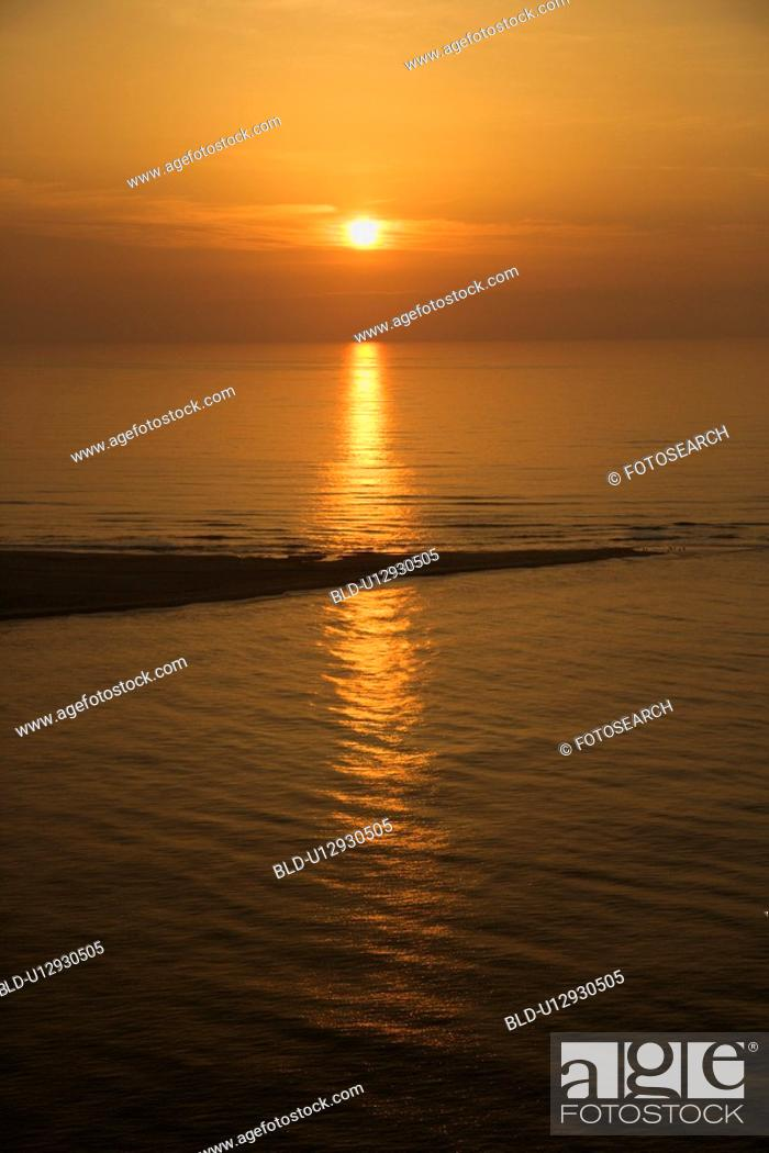 Stock Photo: Sunset over ocean with breakwater.